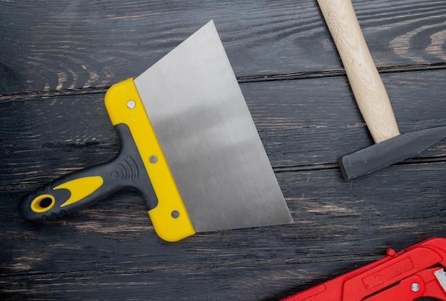 Draufsicht der bauwerkzeuge als spachtel und ziegelhammer auf hölzernem hintergrund Kostenlose Fotos