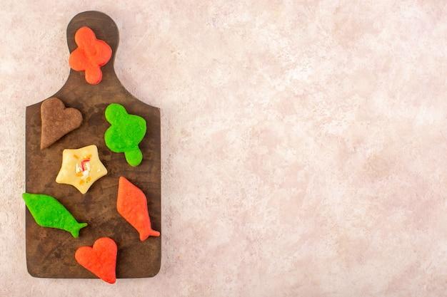 Draufsicht der bunten köstlichen kekse anders gebildet auf dem braunen hölzernen schreibtisch Kostenlose Fotos