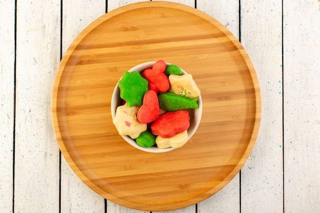 Draufsicht der bunten köstlichen kekse verschieden geformter mehrfarbiger innenplatte auf dem hölzernen schreibtisch Kostenlose Fotos