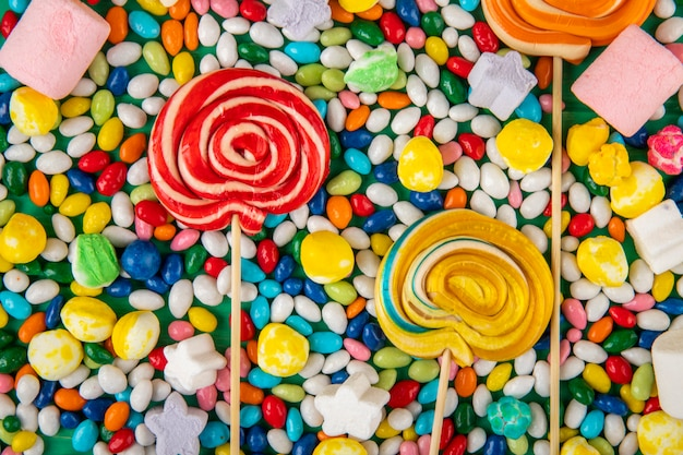 Draufsicht der bunten lutscher auf bonbons im mehrfarbigen glasurhintergrund Kostenlose Fotos