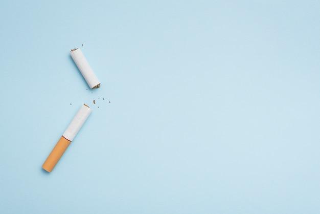 Draufsicht der defekten zigarette auf blauem hintergrund Kostenlose Fotos