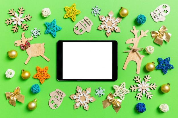 Draufsicht der digitalen tablette auf grün mit spielwaren und dekorationen des neuen jahres Premium Fotos
