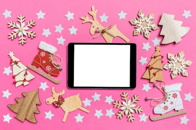 Draufsicht der digitalen tablette, rosa verziert mit festlichen spielwaren und weihnachtssymbolren und bäumen des neuen jahres Premium Fotos