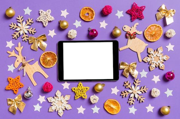 Draufsicht der digitalen tablette umgeben mit spielwaren und dekorationen des neuen jahres auf purpur. Premium Fotos