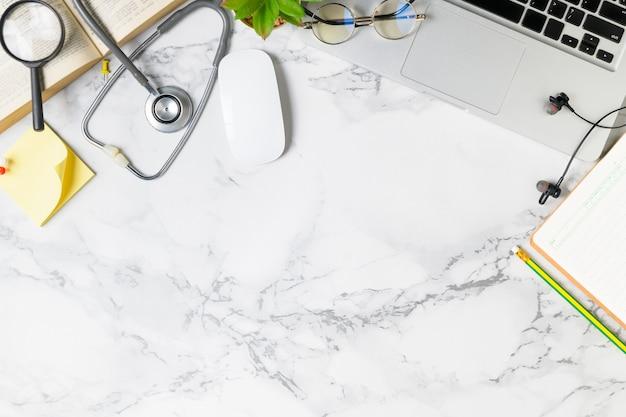 Draufsicht der doktorschreibtisch-marmortabelle mit stethoskop Premium Fotos
