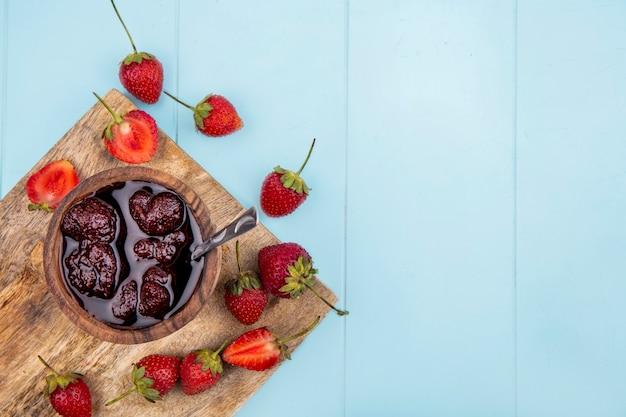 Draufsicht der erdbeermarmelade auf einer hölzernen schüssel mit frischen erdbeeren auf einem weißen hintergrund mit kopienraum Kostenlose Fotos