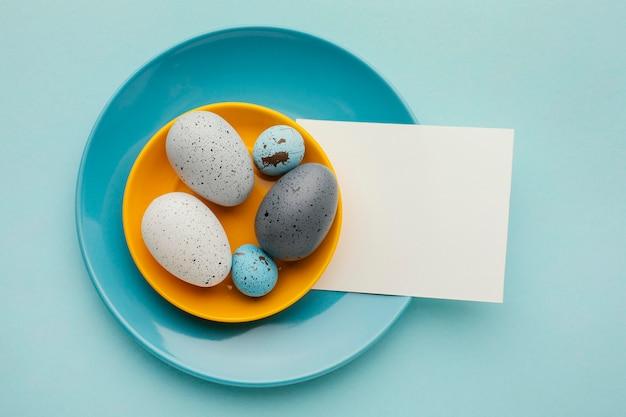 Draufsicht der farbigen ostereier auf tellern mit papier Kostenlose Fotos