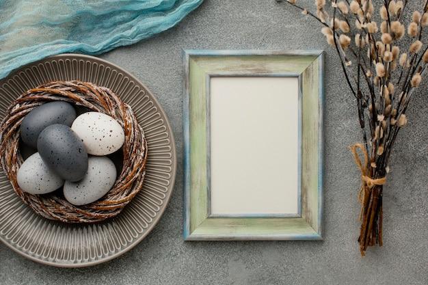 Draufsicht der farbigen ostereier im korb mit rahmen und zweigen Kostenlose Fotos