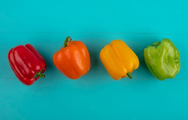 Draufsicht der farbigen paprika auf einer türkisfarbenen oberfläche Kostenlose Fotos
