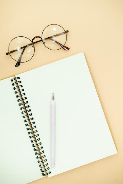 Draufsicht der flachen lage foto des bleistifts, der gläser und des notizblockes Premium Fotos