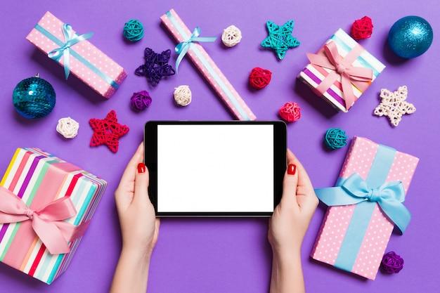Draufsicht der frau tablette in ihren händen auf dem purpur halten gemacht von den weihnachtsdekorationen. Premium Fotos