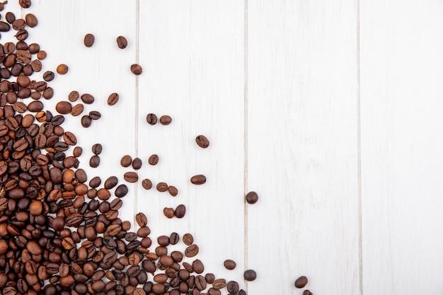 Draufsicht der frisch gerösteten kaffeebohnen lokalisiert auf einem weißen hölzernen hintergrund mit kopienraum Kostenlose Fotos