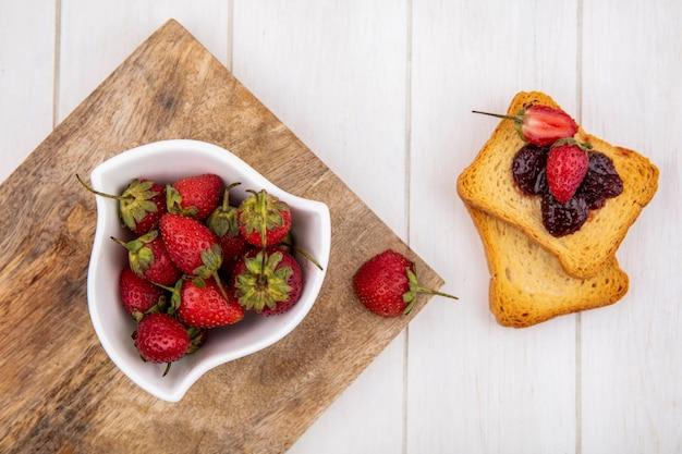 Draufsicht der frischen erdbeeren auf einer weißen schüssel auf einem hölzernen küchenbrett mit gerösteten brotscheiben auf einem weißen hölzernen hintergrund Kostenlose Fotos
