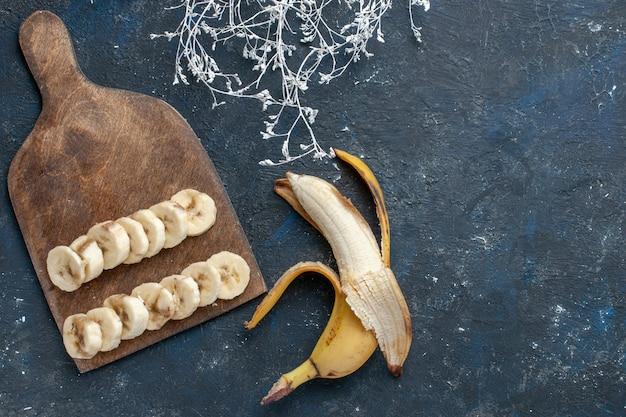 Draufsicht der frischen gelben banane süß und lecker geschnitten auf dunklem schreibtisch, fruchtfrucht süßes vitamin gesundheit Kostenlose Fotos