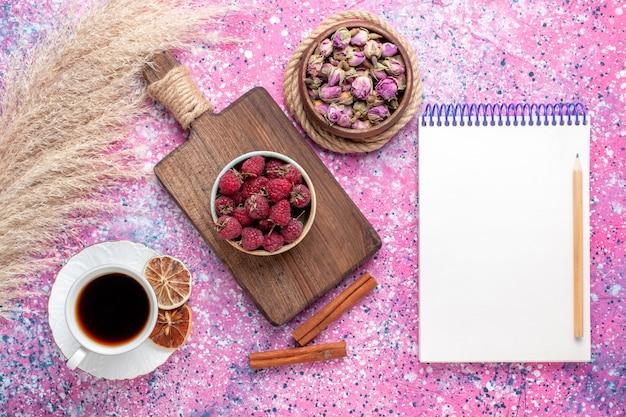 Draufsicht der frischen leckeren himbeeren innerhalb des weißen tellers mit tee und zimt auf der rosa oberfläche Kostenlose Fotos