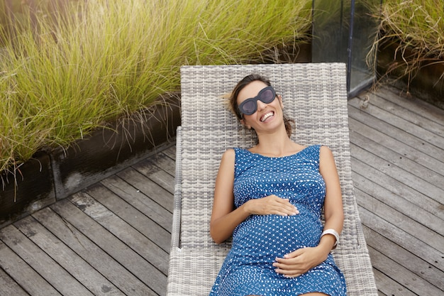 Draufsicht der fröhlichen schwangeren frau, die stilvolle schatten trägt, die auf sonnenliege liegen und hände auf ihrem bauch halten. lächelnde schöne frau, die kind erwartet, das ruhe während der ferien am gesundheitsresort hat Kostenlose Fotos