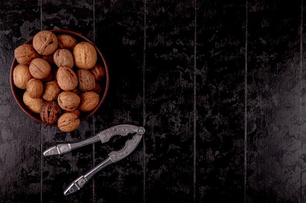 Draufsicht der ganzen walnüsse in einer hölzernen schüssel auf schwarzem hintergrund mit kopienraum Kostenlose Fotos