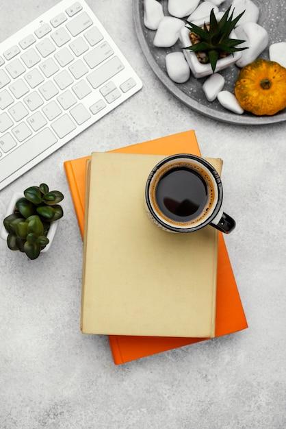 Draufsicht der gebundenen bücher auf schreibtisch mit kaffee und pflanze Kostenlose Fotos