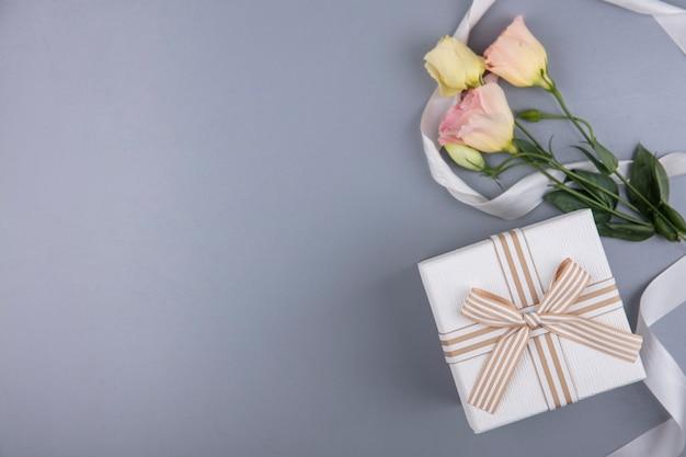 Draufsicht der geschenkbox und der blumen mit band auf grauem hintergrund mit kopienraum Kostenlose Fotos