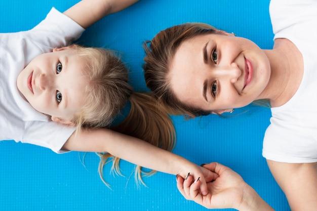 Draufsicht der glücklichen mutter, die mit tochter auf yogamatte aufwirft Kostenlose Fotos