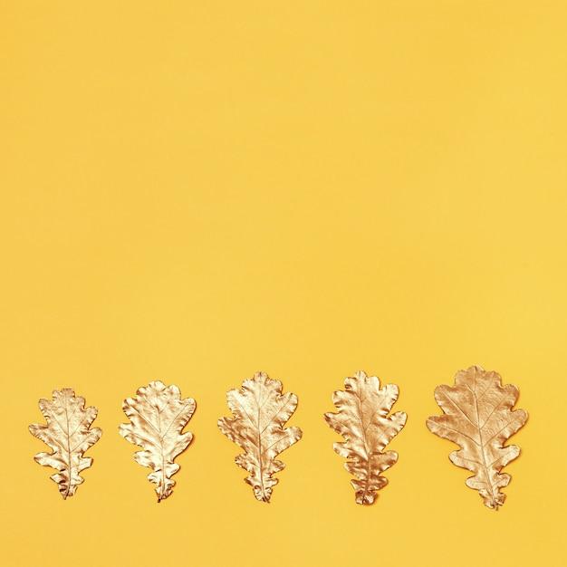 Draufsicht der goldenen gemalten blätter von eichen auf gelbem hintergrund. herbstliche grußkarte. von oben betrachten. Premium Fotos