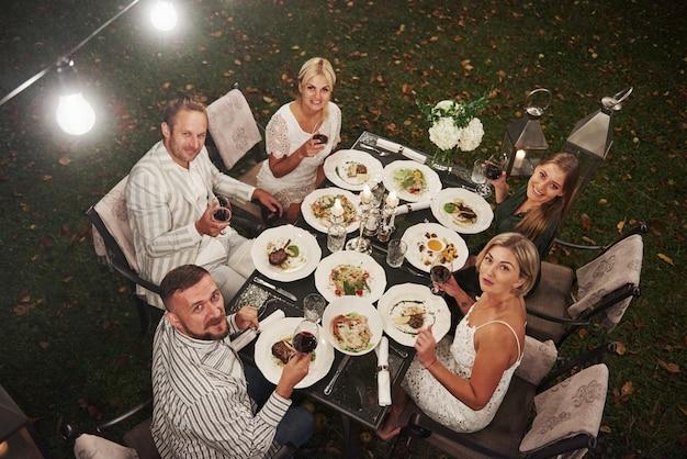 Draufsicht der gruppe von freunden in der eleganten kleidung haben luxuriöses abendessen Premium Fotos