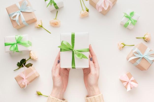 Draufsicht der hände, die geschenk mit blumen halten Kostenlose Fotos