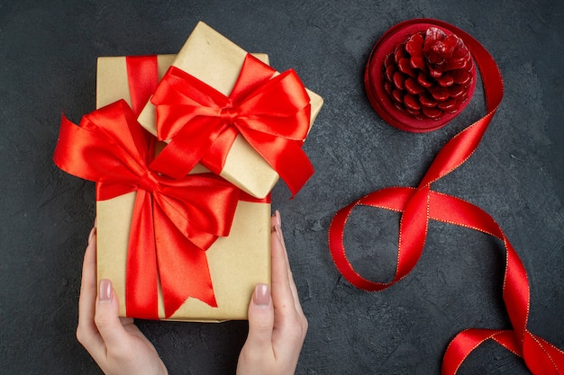 Draufsicht der hand, die schöne geschenke und nadelbaumkegel auf dunklem hintergrund hält Kostenlose Fotos