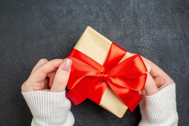 Draufsicht der hand, die schönes geschenk mit bogenförmigem band auf dunklem hintergrund hält Kostenlose Fotos