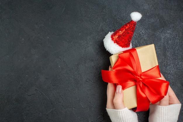 Draufsicht der hand, die schönes geschenk mit bogenförmigem band neben weihnachtsmannhut auf dunklem hintergrund hält Kostenlose Fotos