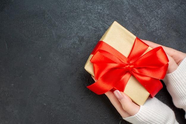 Draufsicht der hand, die schönes geschenk mit bogenförmigem rotem band auf der seite auf dunklem hintergrund hält Kostenlose Fotos