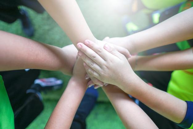 Draufsicht der handgeste des hochs fünf kinder im juniorfußballteam Premium Fotos