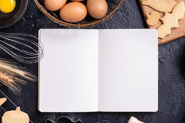 Draufsicht der herstellung von halloween-desserts durch lesen des kochbuchs Premium Fotos