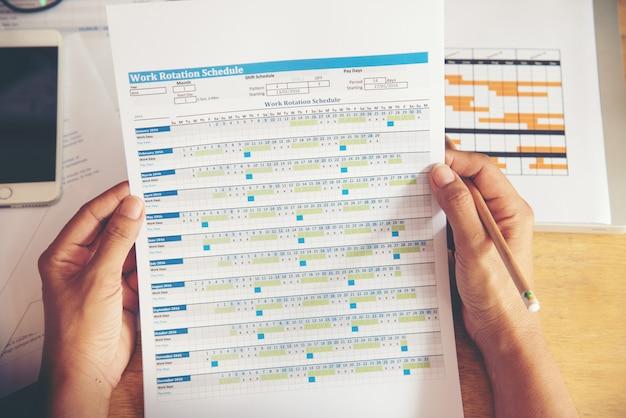 Draufsicht der jungen berufstätigen frau, die laptop verwendet und bericht, diagramme, diagramme, dokument bei der arbeit liest. geschäftsfrau, die an ihrem schreibtisch arbeitet. Premium Fotos