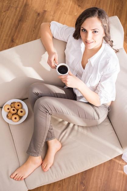 Draufsicht der jungen frau mit einem tasse kaffee. Premium Fotos