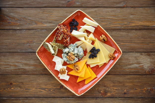 Draufsicht der käseplatte mit cheddarkäse, gouda, weiß und blauschimmelkäse Kostenlose Fotos