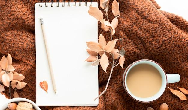 Draufsicht der kaffeetasse mit herbstlaub und notizbuch Kostenlose Fotos