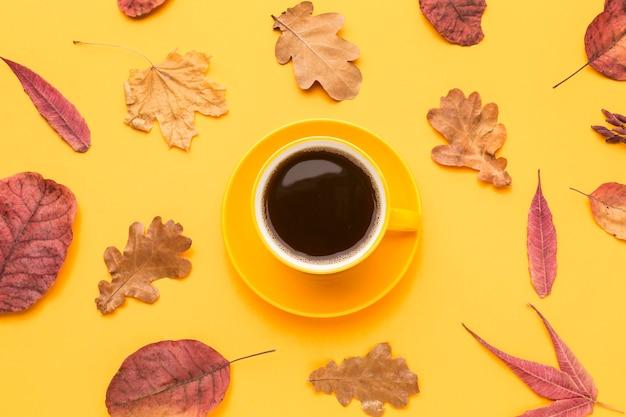 Draufsicht der kaffeetasse mit herbstlaub und platte Kostenlose Fotos