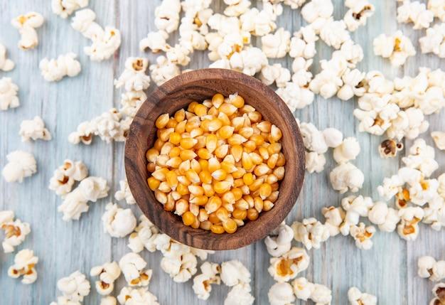 Draufsicht der körner auf hölzerner schüssel mit popcorn lokalisiert auf grau Kostenlose Fotos