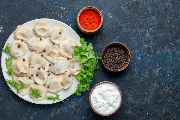 Draufsicht der köstlichen gebackenen knödel innerhalb des tellers zusammen mit joghurt und gemüse auf dunkelgrauem schreibtisch, teig abendessen fleisch kalorien mahlzeit essen Kostenlose Fotos