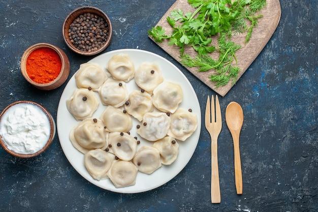 Draufsicht der köstlichen gebackenen knödel innerhalb des tellers zusammen mit pfeffer und grün auf dunklem schreibtisch, teigmahlzeitnahrungsmittelessen-fleischkalorie Kostenlose Fotos