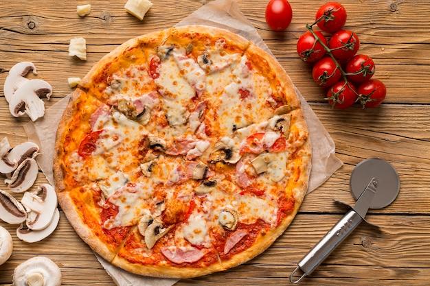 Draufsicht der köstlichen pizza auf holztisch Kostenlose Fotos