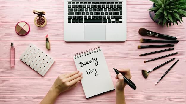 Draufsicht der kreativ dekorierten komposition mit kosmetik, make-up-werkzeugen, zubehör und frauenhänden, die auf notizbuch auf farboberfläche schreiben. beauty-, mode- und einkaufskonzept. Premium Fotos