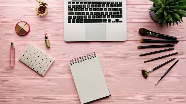Draufsicht der kreativ dekorierten komposition mit kosmetika, make-up-werkzeugen, make-up-produkten, notizbuch und laptop auf farboberfläche. beauty-, mode- und einkaufskonzept. Premium Fotos