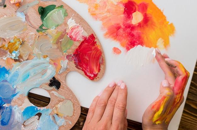 Draufsicht der künstlermalerei unter verwendung der hände Kostenlose Fotos
