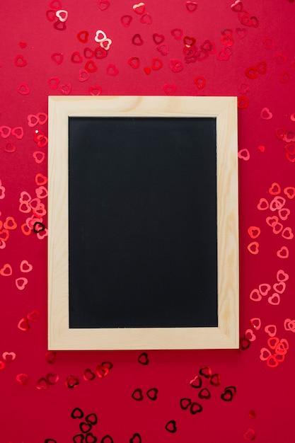 Draufsicht der leeren tafel auf rotem hintergrund mit glänzendem confett. Premium Fotos