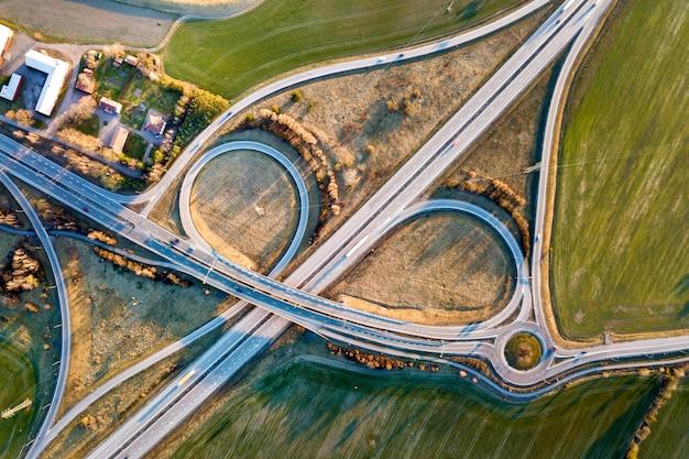 Draufsicht der luft der modernen landstraßenstraßenkreuzung, hausdächer auf frühlingsgrünfeld Premium Fotos