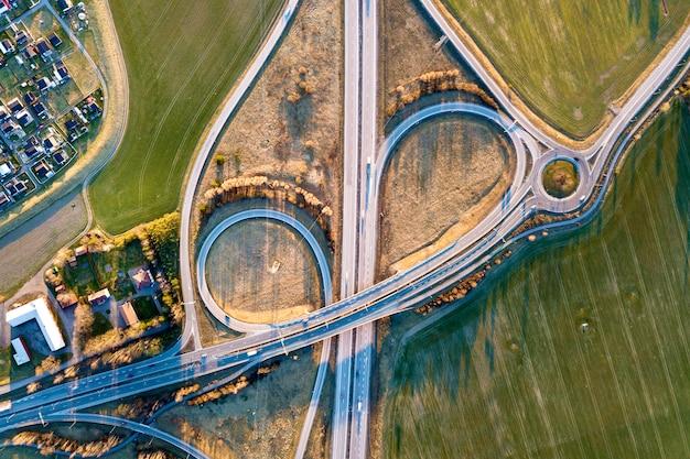Draufsicht der luft der modernen landstraßenstraßenkreuzung, hausdächer auf frühlingsgrünfeldhintergrund. drohnenfotografie. Premium Fotos