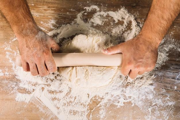 Draufsicht der männlichen bäckerhand, die teig mit nudelholz auf holztisch flach macht Kostenlose Fotos