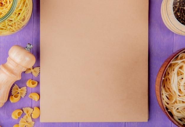 Draufsicht der makkaronis als gekochte und ungekochte spaghetti farfalle pipe-rigate mit schwarzem pfeffer um notizblock auf lila hintergrund mit kopienraum Kostenlose Fotos